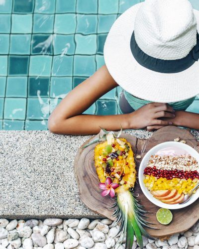 Girl,Relaxing,And,Eating,Fruit,Plate,By,The,Hotel,Pool.